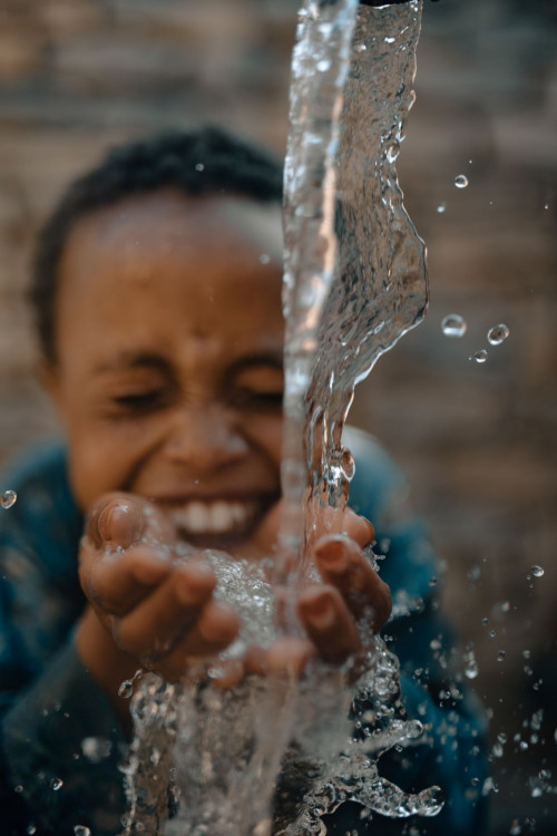 charity: water - boy smiling drinking fresh water